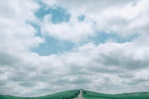 narrow path in hilly valley against cloudy sky