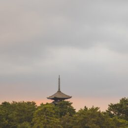 old buddhist shrine among trees under clouds